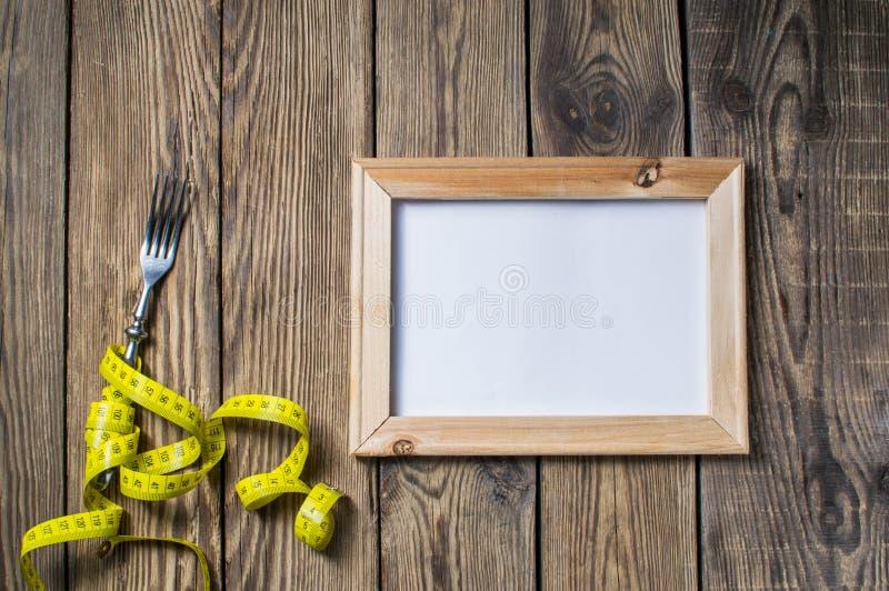 Diety pojęcie, rozwidlenie i pomiarowa taśma na drewnianym tle, Rozwidlenie i pomiarowa taśma na drewnianym tle dla zdrowego styl obrazy stock
