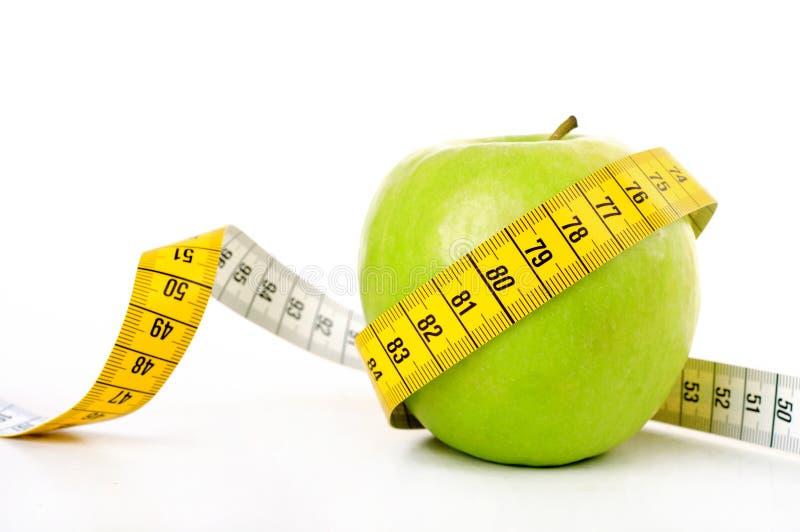 Zielony jabłko z pomiarową taśmą obraz royalty free