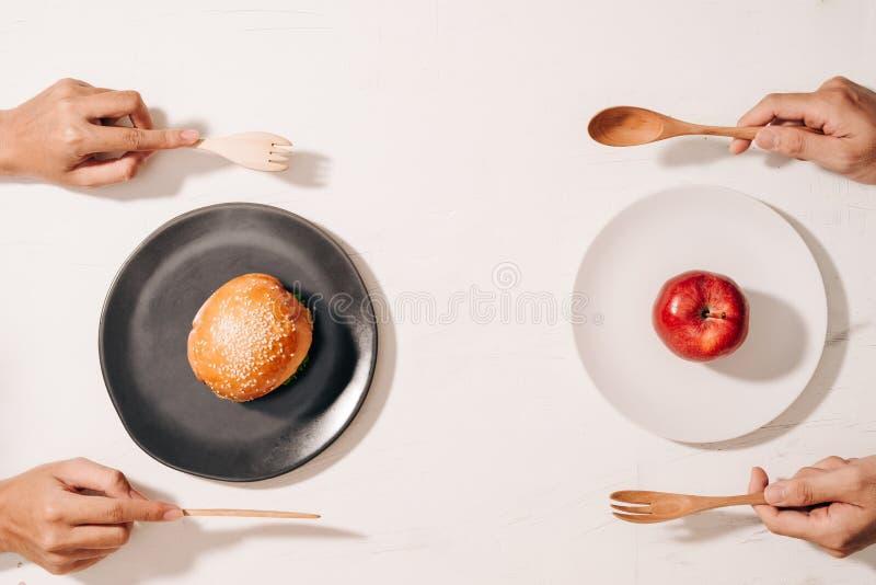 Diety walka i decydować między odżywianie wyborowym dylematem między zdrowym dobrym świeżym owoc i warzywo lub cholesterolu bogac zdjęcia royalty free