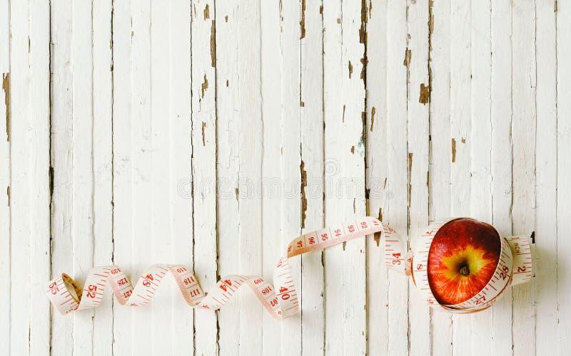 Diety zdrowy pojęcie Czerwony jabłko z pomiarową taśmą na bielu zaleca się zdjęcia stock