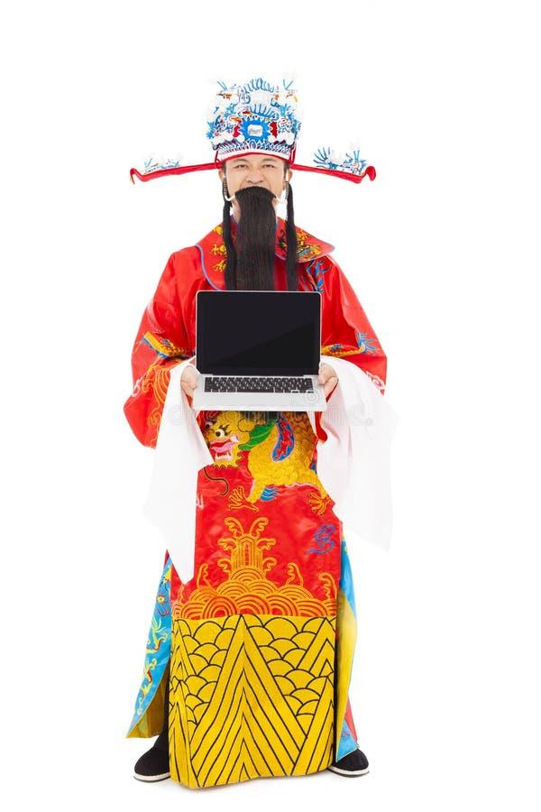 Dieu de la richesse tenant et tenant un ordinateur portable photographie stock