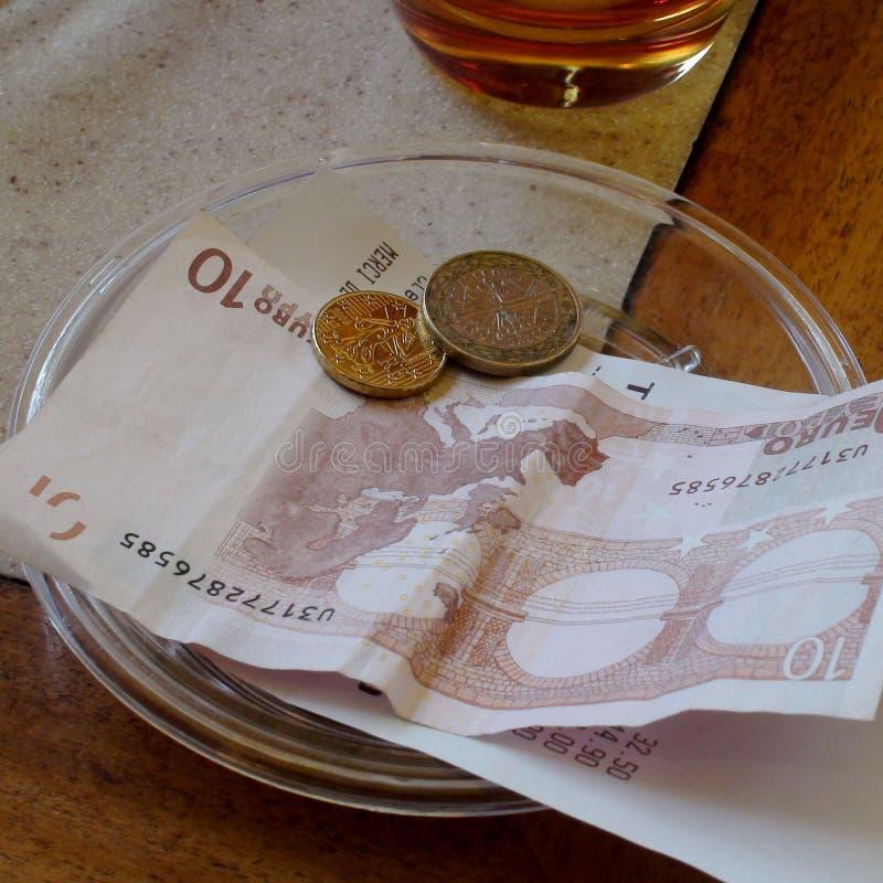 Diez euro Bill con las monedas en la placa en la tabla de madera en restaurante fotografía de archivo libre de regalías