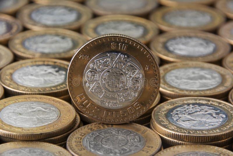 Diez peso mexicanos sobre mà ¡ s monedas alineadas y apiladas