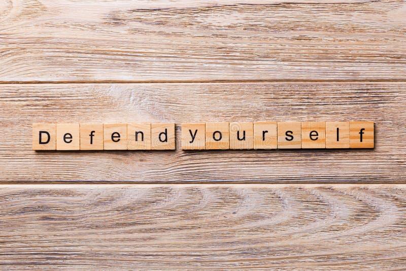 Difenda parola scritta sul blocco di legno difenda testo sulla tavola di legno per vostro desing, concetto fotografie stock libere da diritti
