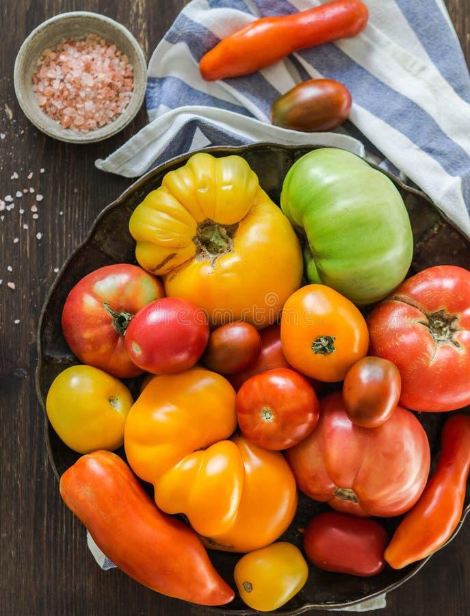Diferente de tamaño y el color, tomates en un metal ruede en una toalla de cocina, sal del mar en un cuenco fotografía de archivo