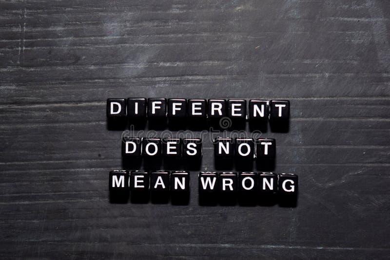 Diferente não significa erradamente em blocos de madeira Conceito da educa??o, da motiva??o e da inspira??o fotografia de stock royalty free