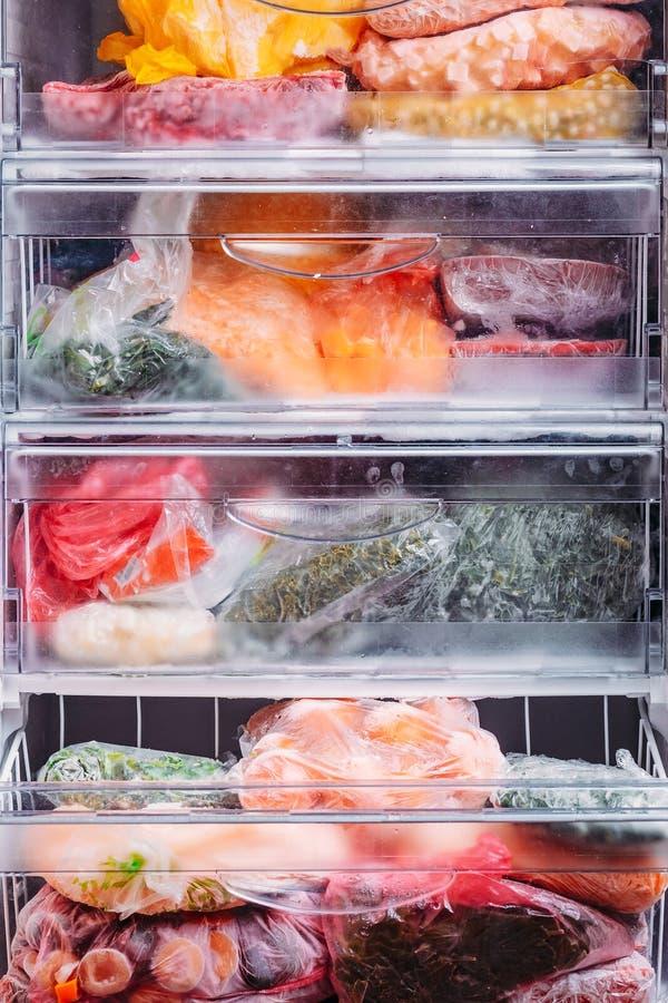 Diferente tipo de verduras congeladas en las bolsas de plástico en un refrigerador imagenes de archivo
