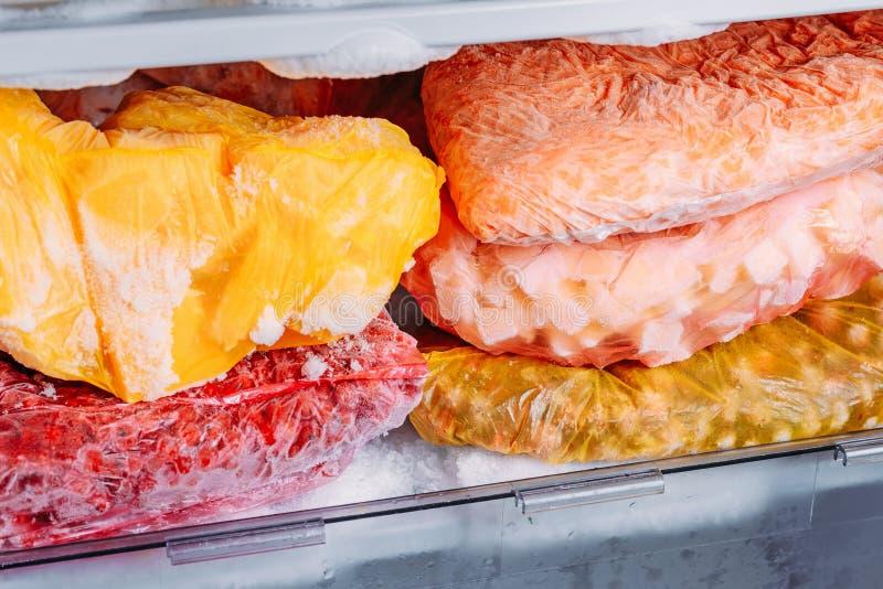 Diferente tipo de verduras congeladas en las bolsas de plástico en un refrigerador fotografía de archivo