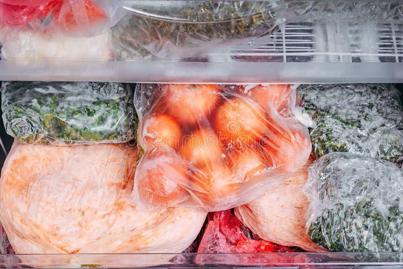 Diferente tipo de verduras congeladas en las bolsas de plástico en un refrigerador imagen de archivo libre de regalías
