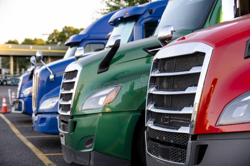Diferentes fazem caminhões-caminhões grandes ficarem na fila no estacionamento do caminhão marcado com linhas foto de stock