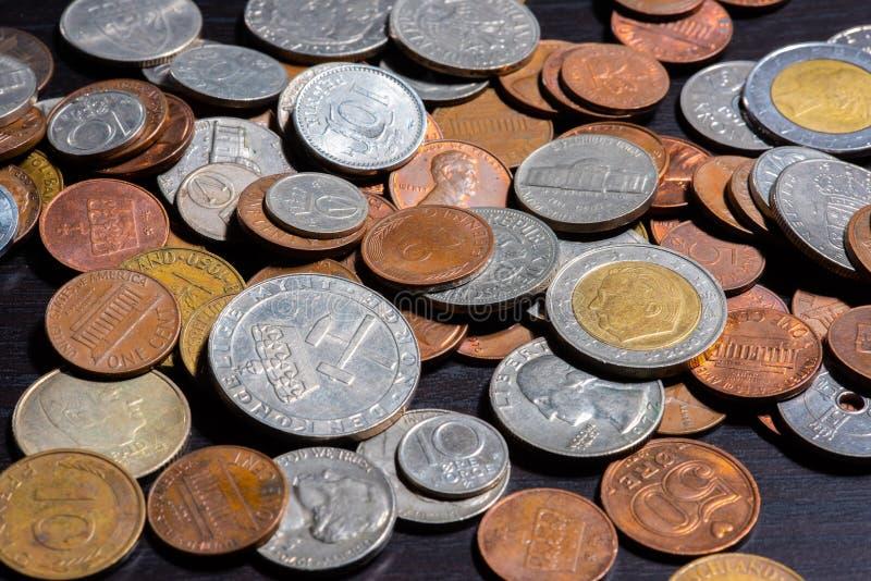 Diferentes tipos de monedas en una tabla negra fotos de archivo