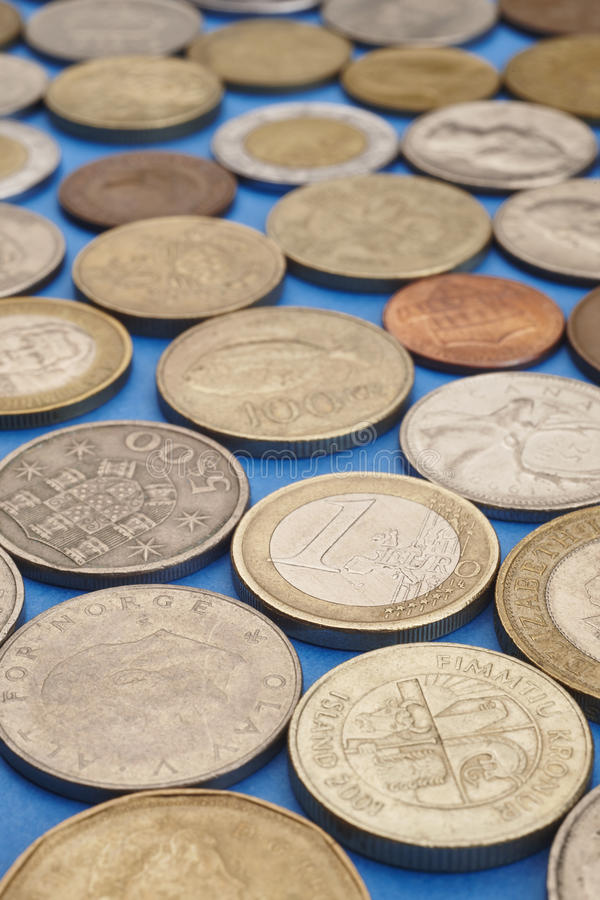 Diferentes tipos de monedas sobre un fondo azul Detalle macro foto de archivo libre de regalías
