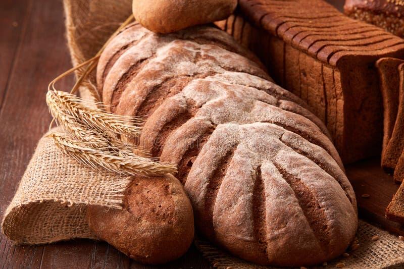 Diferentes tipos de pan en la arpillera en la tabla de madera Diseño del cartel de la cocina o de la panadería foto de archivo libre de regalías