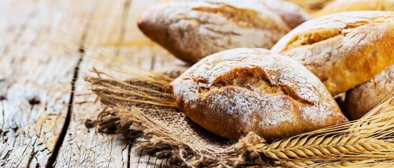 Diferentes tipos de pan fresco en la tabla de madera surtido de pan en fondo marrón imagen de archivo