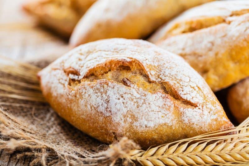 Diferentes tipos de pan fresco en la tabla de madera surtido de pan en fondo marrón foto de archivo