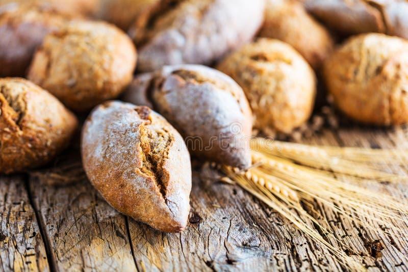 Diferentes tipos de pan fresco en la tabla de madera surtido de pan en fondo marrón fotos de archivo libres de regalías