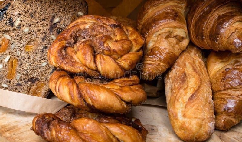 Diferentes tipos de pan y de bollos a bordo desde arriba Diseño del cartel de la cocina o de la panadería foto de archivo libre de regalías