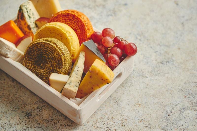 Diferentes tipos frescos y deliciosos de quesos colocados en cajón de madera con las uvas fotografía de archivo libre de regalías