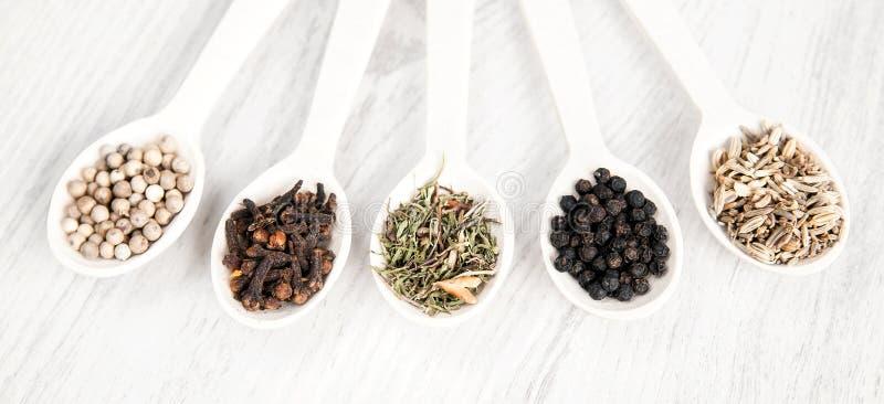 Différentes épices et herbes dans des cuillères en bois sur le fond blanc de table Poivre noir et blanc, clou de girofle, savoure images libres de droits