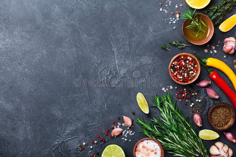 Différentes épices et herbes sur la vue supérieure en pierre noire de table Ingrédients pour la cuisson Fond de nourriture images libres de droits