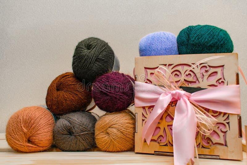 Différentes boules colorées de fil de fil de textile Rangée de longue laine pliée large sur le gisement de boîte de profondeur Bo image stock