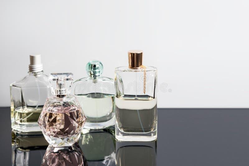 Différentes bouteilles de parfum avec des réflexions Parfumerie, cosmétiques L'espace libre pour le texte photos stock