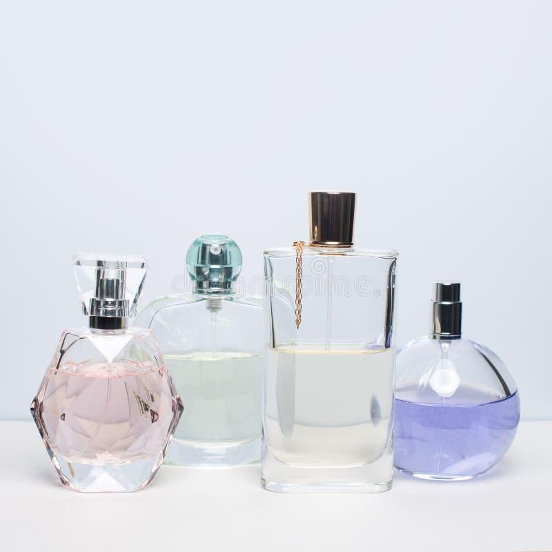 Différentes bouteilles de parfum sur le fond blanc Parfumerie, cosmétiques image libre de droits