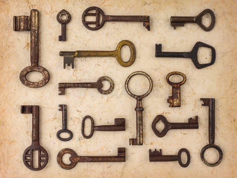Différentes clés antiques sur un rétro fond de papier photos stock