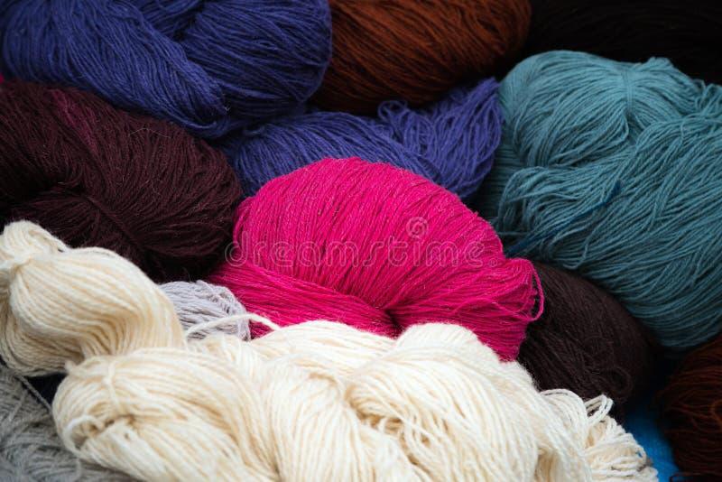 Différentes couleurs des boules de fil à tricoter empilées sur l'un l'autre photo stock