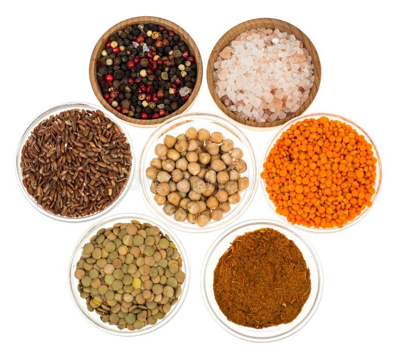 Différentes cuvettes avec des épices, des céréales et des herbes sur le fond blanc photo libre de droits