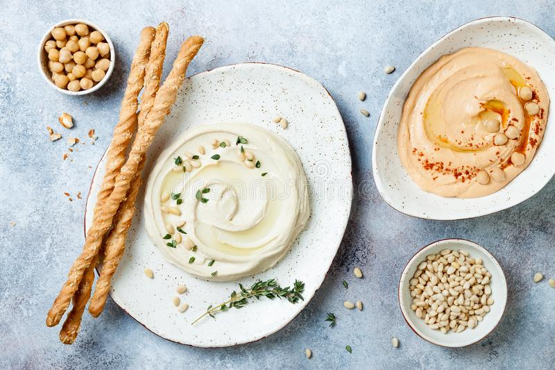 Différentes cuvettes faites maison de houmous Houmous traditionnel avec le thym, les pignons d'huile d'olive et et le poivre ou l images stock