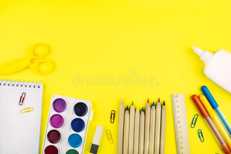 Différentes fournitures scolaires sur le fond de papier jaune lumineux photographie stock