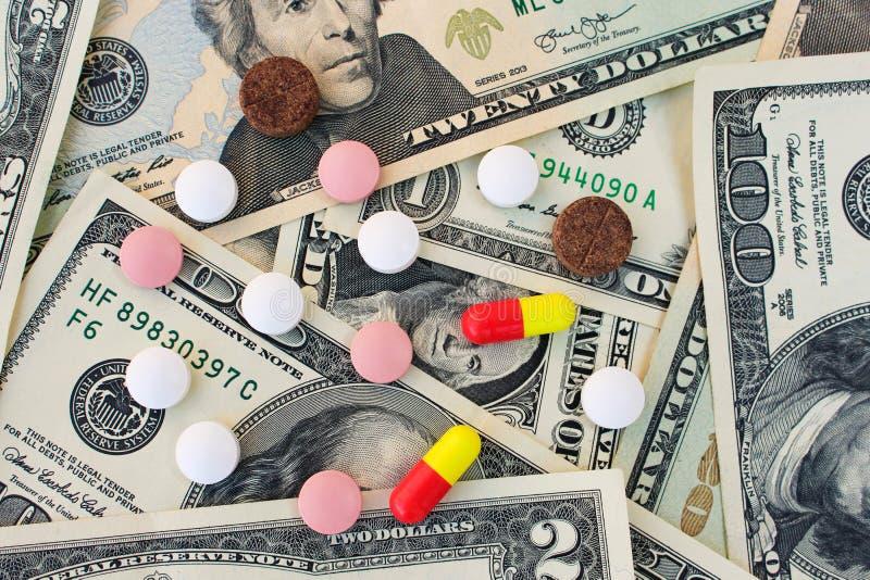 Différentes pilules médicales sur le fond des dollars photos libres de droits