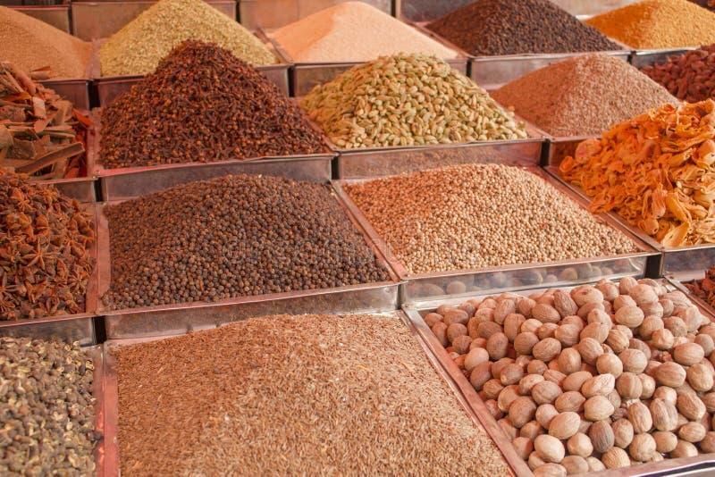 Différentes poudres et graines colorées indiennes d'épice dans des plateaux carrés en métal sur le compteur images stock
