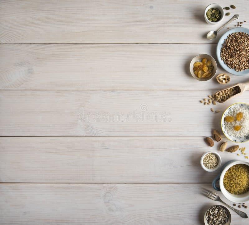 Différents écrous, céréales, raisins secs des plats sur une table en bois Cèdre, anarcadier, noisette, noix, amandes, graines de  photos libres de droits