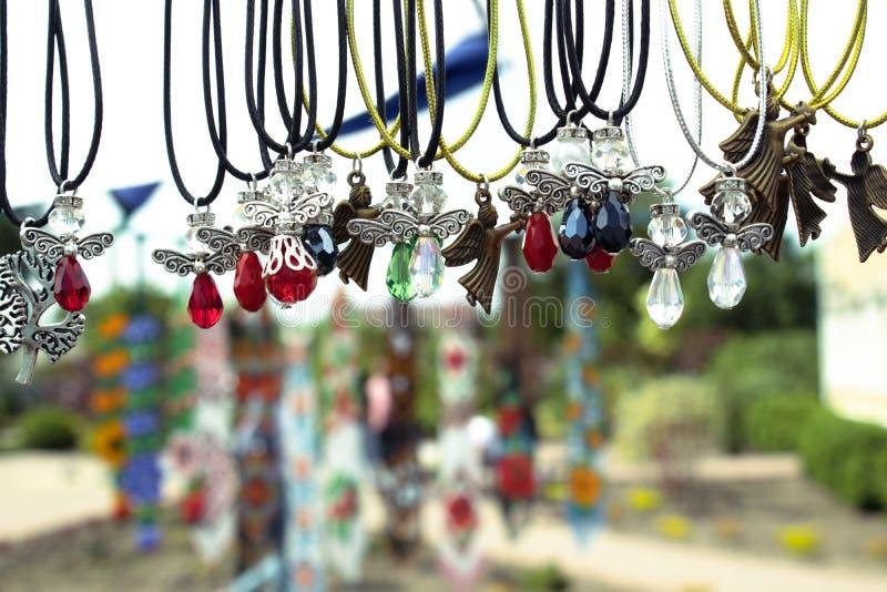 Différents colliers de diverses formes et couleurs avec les pierres colorées sur un fond brouillé photo stock