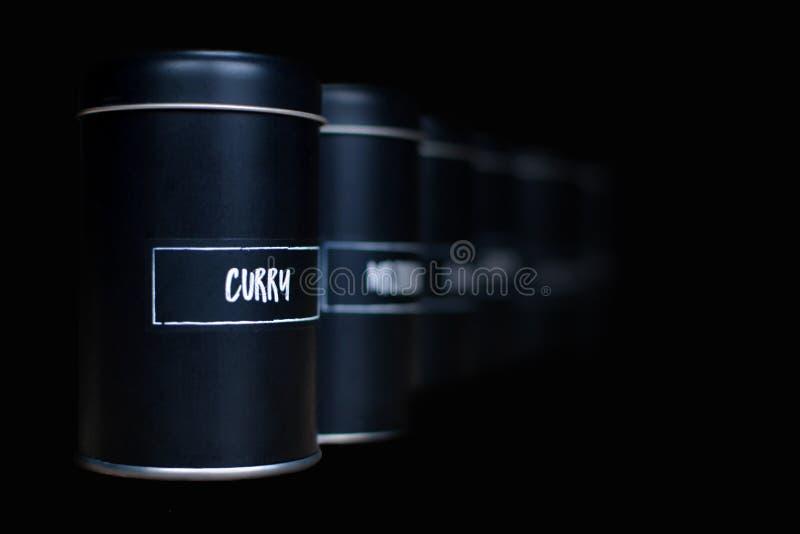 Différents dispositifs trembleurs noirs d'épice dans une rangée se fanant sur le fond foncé avec le label blanc de cari dans l'av photographie stock