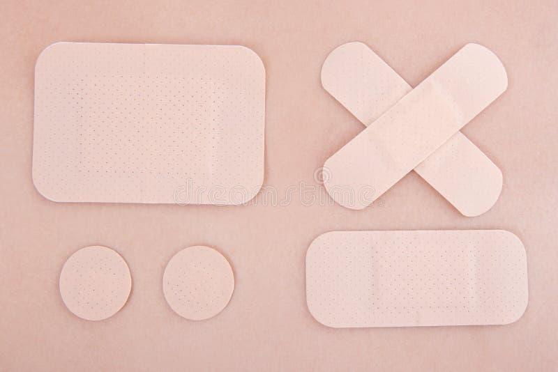 Différents emplâtres adhésifs médicaux sur le fond de peau photographie stock libre de droits