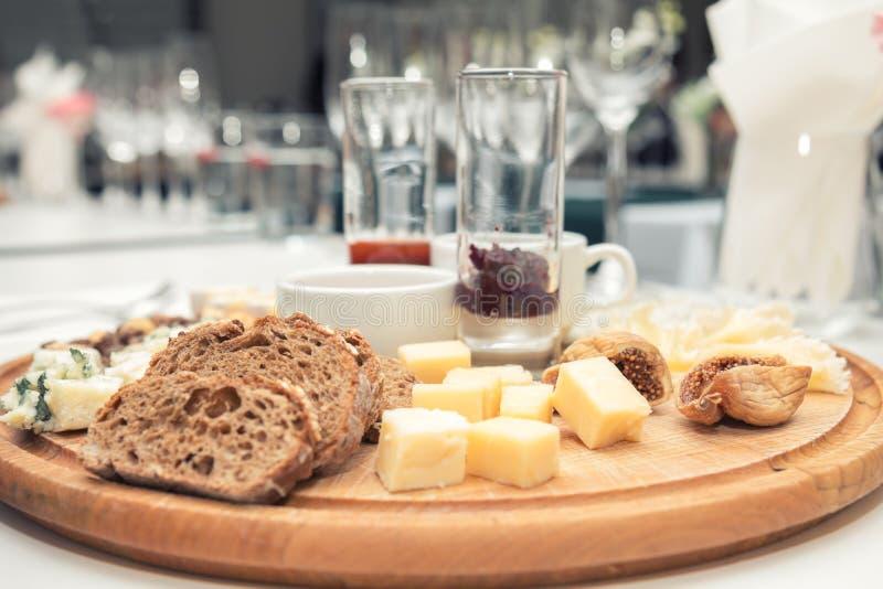 Différents fromages délicieux sur le conseil rond en bois images stock