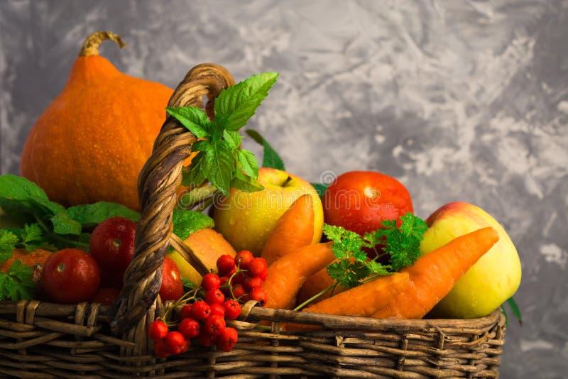 Différents fruits et légumes dans le panier en osier sur le backgro gris photos libres de droits