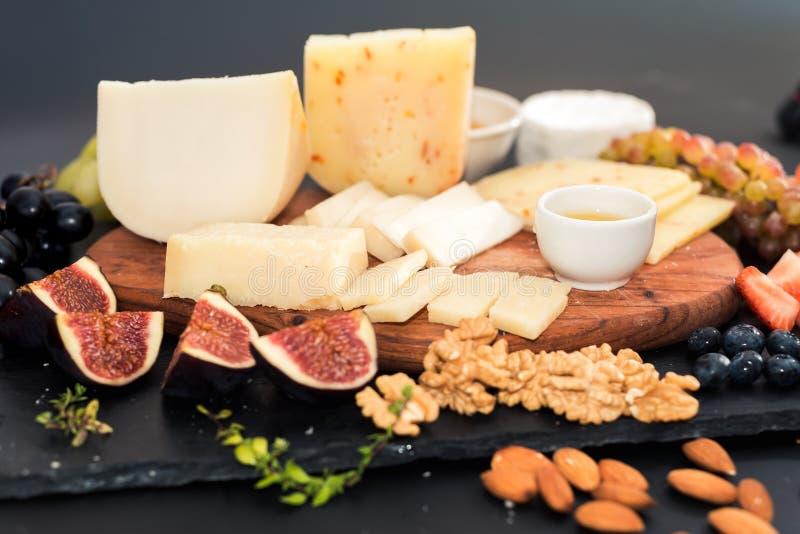différents genres de fromages, de miel, de figues, d'écrous, de raisins, et de fruit sur une table Foyer sélectif Copiez l'espace photos libres de droits
