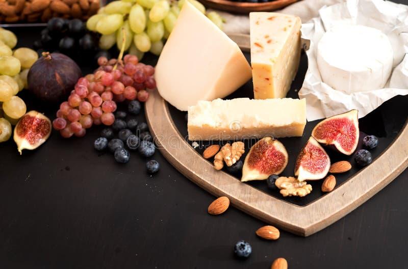 différents genres de fromages, de miel, de figues, d'écrous, de raisins, et de fruit sur une table Foyer sélectif Copiez l'espace photos stock