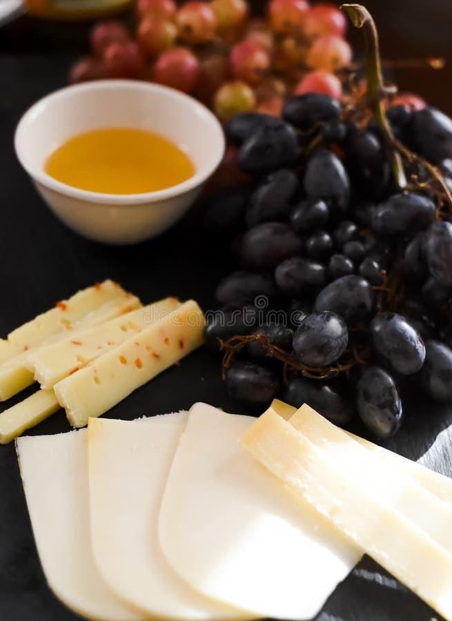différents genres de fromages, miel, raisins sur une table Foyer sélectif Copiez l'espace images stock