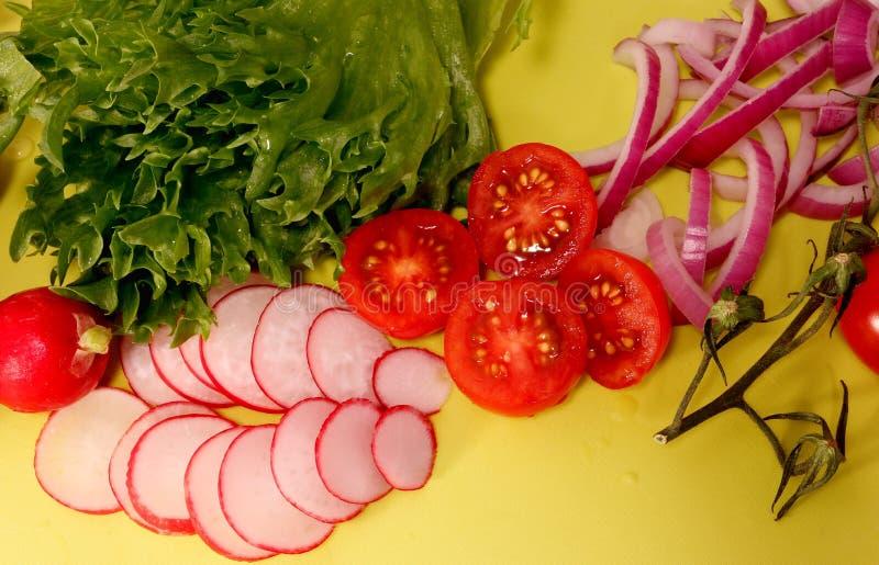 Différents genres de légumes découpés en tranches sur un fond jaune photos libres de droits