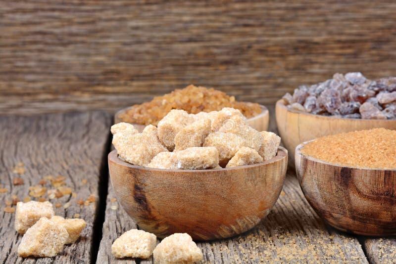 Différents genres de sucre dans cuvettes sur le fond en bois image libre de droits
