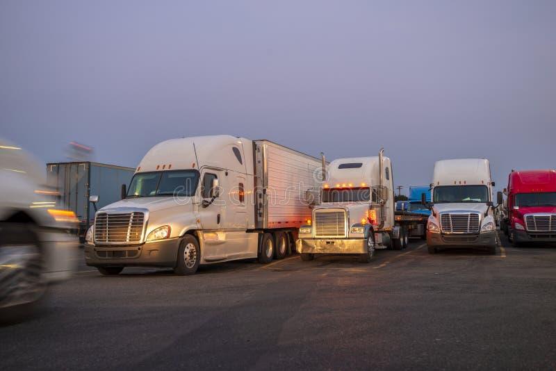 Différents grands d'installations camions semi avec semi des remorques se tenant dans la rangée sur le relais routier crépuscu photo stock