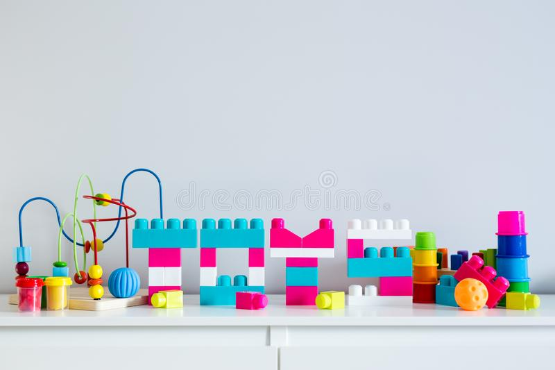 Différents jouets et lettres pliés du constructeur coloré de jouet avec l'espace de copie au-dessus du mur blanc photographie stock libre de droits