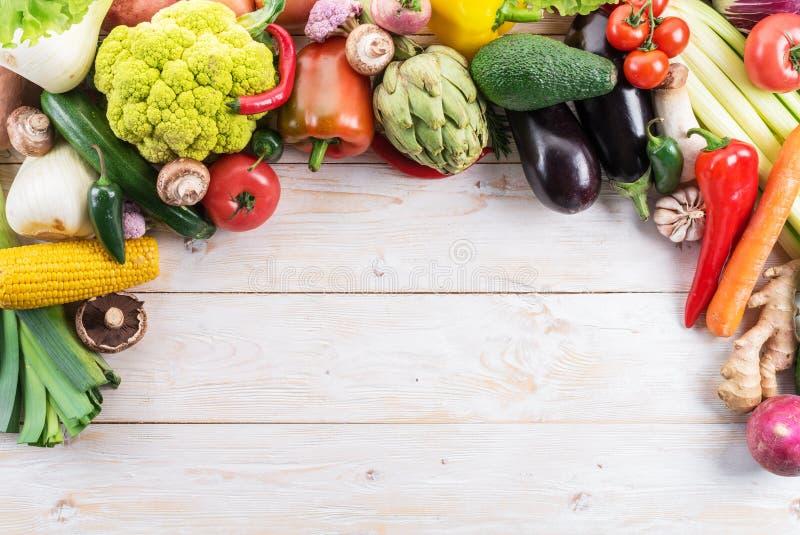 Différents légumes colorés disposés comme cadre Backgr en bois photos stock