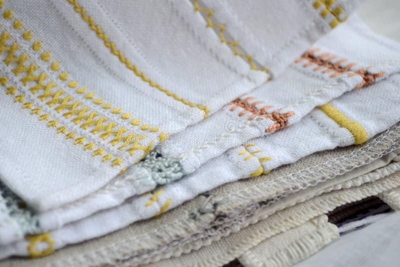Différents modèles jaunes, oranges et bleus de broderie sur le tissu blanc et gris photo stock