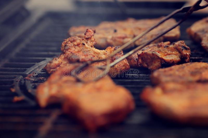 Différents morceaux de viande sont cuits sur un grill en fonte pour un barbecue - premier plan avec des pinces blanches pour l'es photographie stock libre de droits